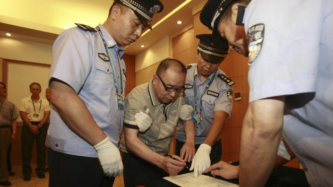 FILE - In this July 23, 2011 file photo released by China's Xinhua news agency, Lai Changxing, center, signs a warrant issued for his arrest as he arrives at the Beijing Capital International Airport in Beijing. Lai once called China's most-wanted fugitive was sentenced to life in prison for smuggling on Friday, May 18, 2012. (AP Photo/Xinhua, Zhang Jianxin, File) NO SALES