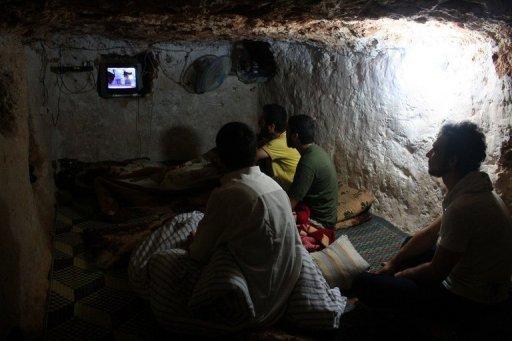 Syrians watch TV at an underground shelter in Al-Bueda, near the city of Homs, on July 24. Watching talk shows and comic soap operas on state television in Syria, one may well wonder whether the country is really in the throes of a deadly crisis