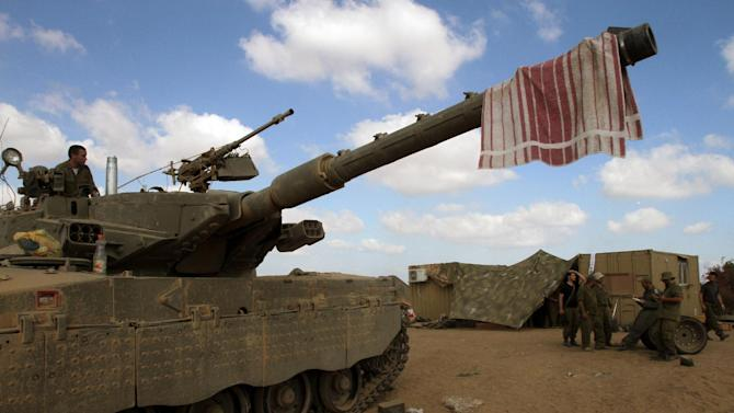 Israeli soldiers rest at an army deployment area along the Israeli border with the Gaza Strip on July 26, 2014