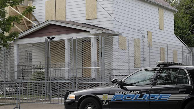 A Cleveland police patrol car sits in front of the boarded up home of Ariel Castro in Cleveland Tuesday, May 14, 2013. Three women were rescued from the house last week after a decade in captivity. Castro is under arrest and charged with rape and kidnapping. (AP Photo/Mark Duncan)