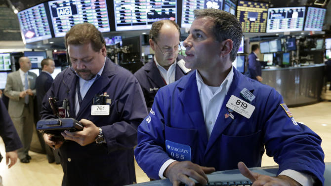 Specialist Anthony Rinaldi, right, works with traders on the floor of the New York Stock Exchange Friday, July 5, 2013. Concern over China's slowdown weighed on Asian stocks Monday July 8, 2013 while European markets regained their footing after last week's stronger-than-expected U.S. jobs report. (AP Photo/Richard Drew)