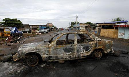 The wreckage of a car burnt during recent clashes between protesters and riot police is used to block a main street in Burundi's capital Bujumbura