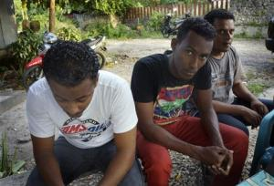 Asylum seekers, who were turned back by Australia, sit in an immigration holding area at a hotel in Kupang