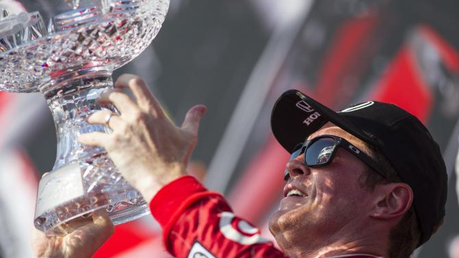 Scott Dixon, of New Zealand, lifts the trophy after winning the IndyCar auto race in Toronto on Sunday, July 14, 2013. (AP Photo/The Canadian Press, Chris Young)