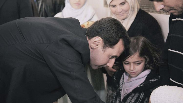 Syria's President Bashar al-Assad speaks with children during his visit to displaced Syrians in the town of Adra in the Damascus countryside