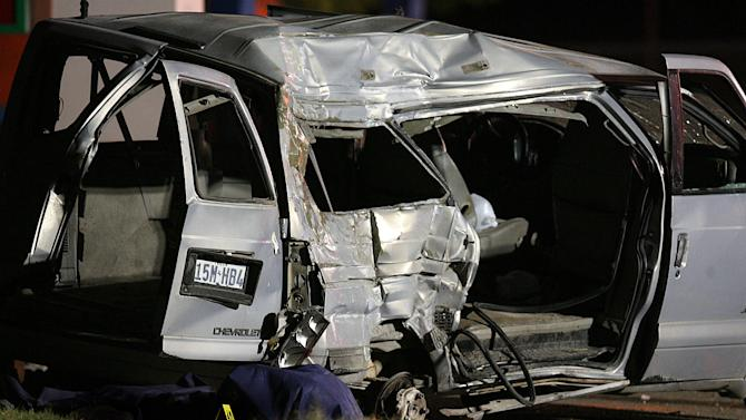 A covered body of a victim lays beside a mini van on Wednesday, April 11, 2012, at the scene of Tuesday's deadly wreck involving a van carrying suspected illegal immigrants in Palmview, Texas. At least nine people were killed and six were hurt in the crash. (AP Photo/The Monitor, Joel Martinez)  MAGS OUT; TV OUT