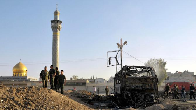 FILE - In this June 14, 2012, file photo released by the Syrian official news agency SANA, Syrian soldiers stand at the explosion site where a car bomb exploded near the shrine of Sayyida Zeinab, visible in the background, suburb of Damascus, Syria. Iraqi Shiites increasingly fear the Muslim sect and its holy sites could be targeted in Syria, and Iranian-linked militants loyal to the faction are girding for a new eruption of retaliatory sectarian fighting, according to Iraqi Shiite leaders and government officials. (AP Photo/SANA, File)