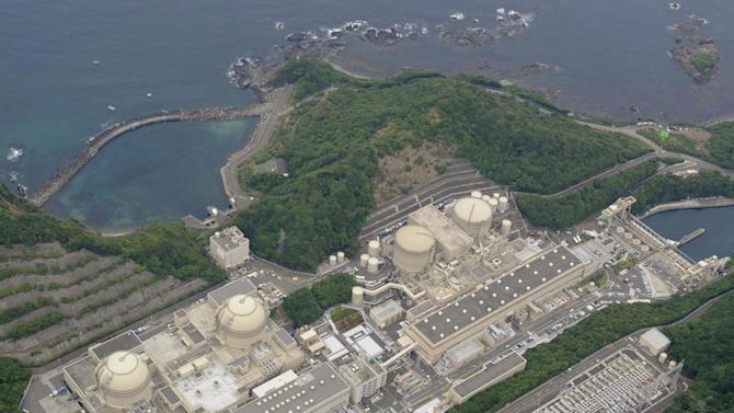 In this June 16, 2012 aerial photo, four round-shaped reactors, obliquely from bottom left, the No. 4, No. 3, No. 2 and No. 1, are seen at Ohi nuclear power plant in Ohi town in Fukui Prefecture, western Japan. Two nuclear reactors have passed safety checks and gotten the Japanese government's approval on June 16 to resume generating power. But communities around the Ohi plant in western Japan feel they aren't ready. If the reactors plunged into a Fukushima-like meltdown, the only route to escape or send help would be a road closed by snow in winter or clogged by beachgoers in summer. (AP Photo/Kyodo News) JAPAN OUT, MANDATORY CREDIT, NO LICENSING IN CHINA, HONG KONG, JAPAN, SOUTH KOREA AND FRANCE