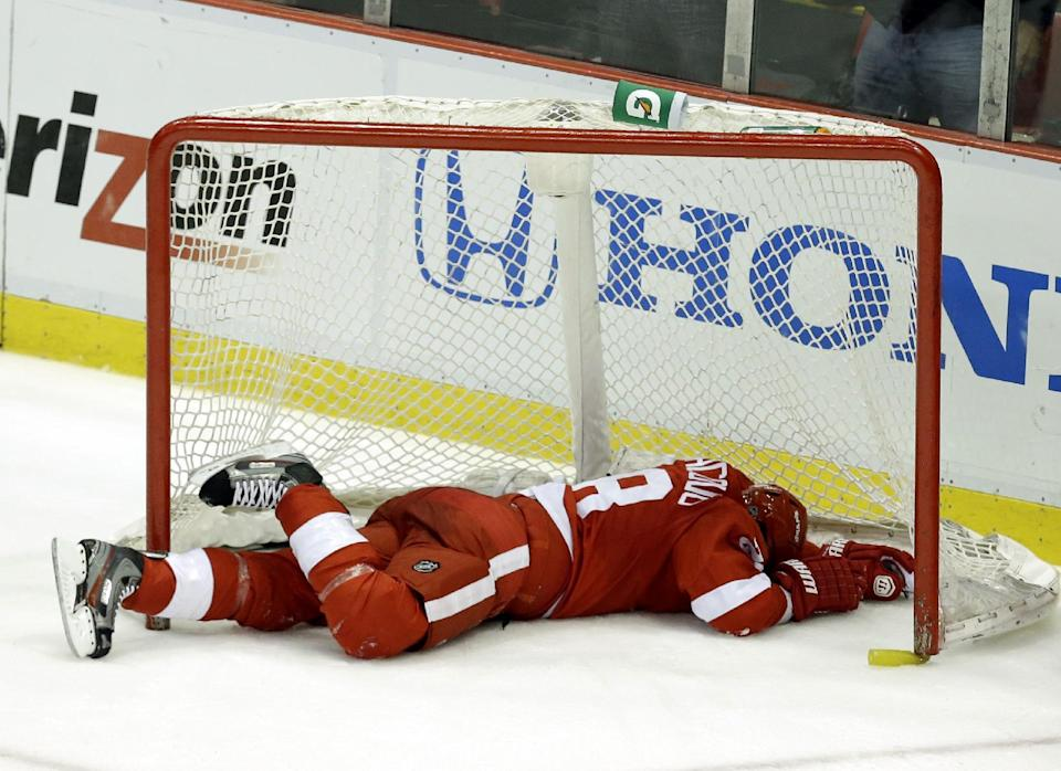 Detroit Red Wings defenseman Carlo Colaiacovo lies in the net after coming off its posts against the Chicago Blackhawks during the third period in Game 4 of the Western Conference semifinals in the NHL hockey Stanley Cup playoffs in Detroit, Thursday, May 23, 2013. (AP Photo/Paul Sancya)
