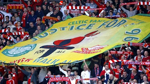 Liverpool supporters hold a banner during a minute of silence in memory of the 96 fans who died in the Hillsborough tragedy (Reuters)