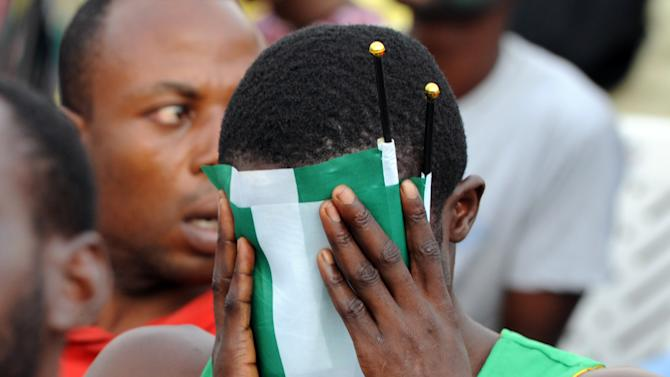 A Nigeria fan covers his face with the country's green and white flag as he watches the 2014 FIFA World Cup round of 16 football match between France and Nigeria at a viewing centre in Lagos on June 30, 2014