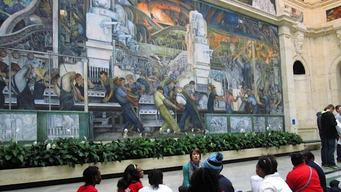 This Dec. 5, 2014 photo shows a class learning about the Detroit Industry Murals at the Detroit Institute of Arts. The murals were done in the 1930s by Diego Rivera as a tribute to Detroit's manufacturing industry, and  Rivera spent time studying the River Rouge Ford car factory. The museum's collection was at one point threatened with a sale to help fund Detroit's pension obligations, but finalization of the city's bankruptcy last week included a deal that protects the art. (AP Photo/Beth J. Harpaz)