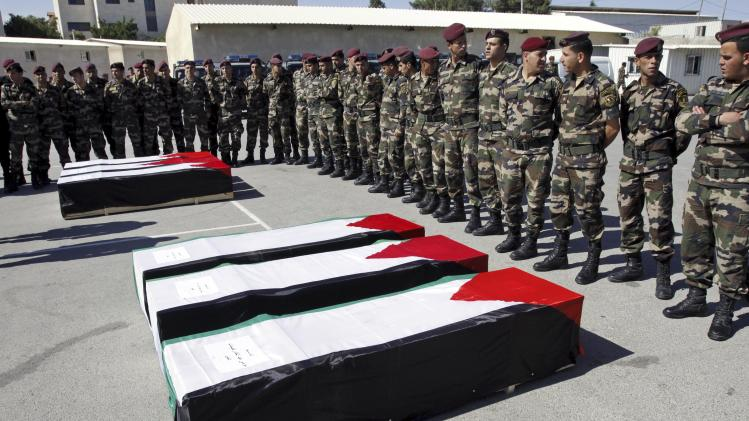 Members of the Palestinian security forces stand around coffins containing the remains of bodies of 91 Palestinian militants transferred from Israel to the Palestinian Authority, in the West Bank city of Ramallah, Thursday, May 31, 2012. Israel transferred the bodies in an effort to induce Palestinian President Mehmoud Abbas to renew negotiations. Palestinian officials said all were killed either while carrying out suicide bombings or other attacks on Israeli targets. (AP Photo/Mohammed Ballas)