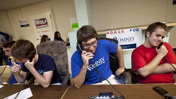 In this photo taken June 29, 2012, Geoffrey Tanner, 19, of Herndon, Va., center, and other volunteers make phone calls at the Romney Victory Office in Fairfax, Va. Call them passionate, idealistic, earnest, even a tad naive: The volunteers helping to power the Obama and Romney campaigns are outliers at a time when polls show record low public satisfaction with government and a growing belief that Washington isn't on their side.  While motivated by opposing goals, the Obama and Romney volunteers share at least one key trait: an abiding faith in the political process and a belief that it still matters who occupies the White House.  (AP Photo/Jacquelyn Martin)