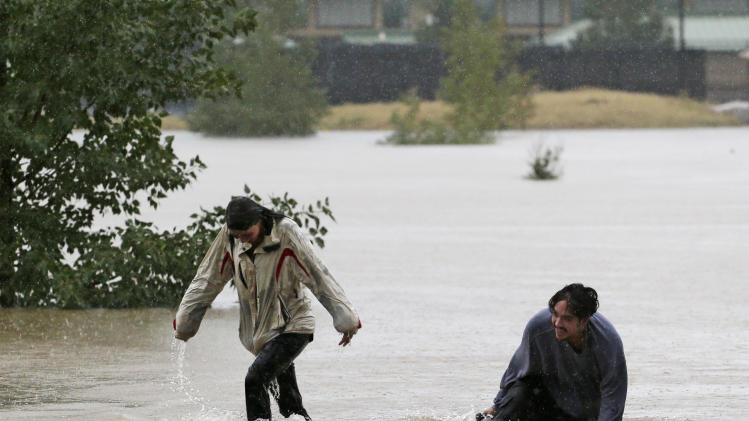 A couple plays in flood water at Utah Park in Aurora, Colo., on Thursday, Sept. 12, 2013. The park was under water due to flooding. Flash flooding in Colorado has cut off access to towns, closed the University of Colorado in Boulder and left at least three people dead.(AP Photo/Ed Andrieski)