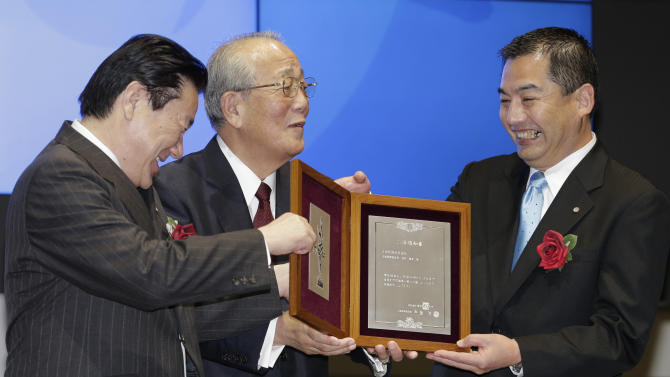 Japan Airlines President Yoshiharu Ueki, left, honorary chairman Kazuo Inamori, center, and chairman Masaru Onishi smile, holding the certificate of the listing issued by the Tokyo Stock Exchange during a ceremony to mark its relisting in Tokyo, Wednesday, Sept. 19, 2012.   Japan Airlines Co. capped an $8.5 billion initial public offering, the biggest this year after Facebook's, with a modest return to the Tokyo Stock Exchange: Its share price rose only 1 percent in the first day of trading. (AP Photo/Shizuo Kambayashi)