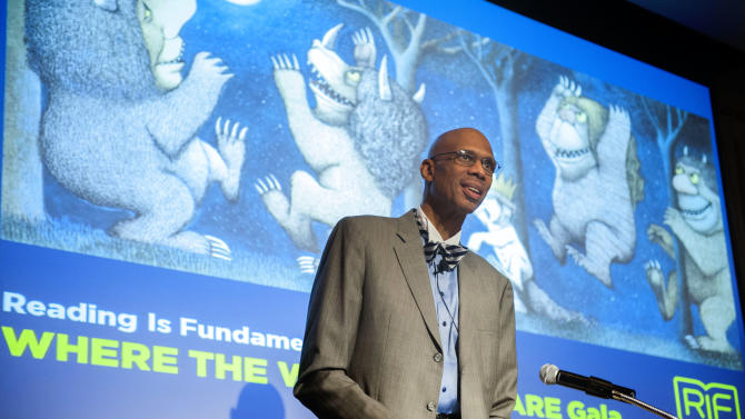 """IMAGE DISTRIBUTED FOR READING IS FUNDAMENTAL - Kareem Abdul-Jabbar reads the classic children's book by Maurice Sencak """"Where the Wild Things Are"""" during the Reading Is Fundamental """"Where the Wild Things Are"""" Gala, Thursday May 9, 2013, at the Four Seasons Hotel in Washington. The nation's oldest children's literacy organization, RIF provided more than 4 million underserved children 10 million new books last year alone. (Kevin Wolf/AP Images for Reading Is Fundamental)"""