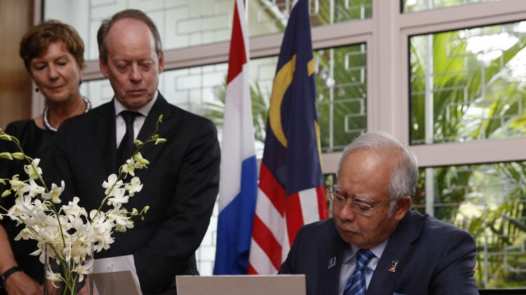 Malaysian Prime Minister Razak, with the Dutch ambassador Molenaar, signs the book of condolence at the residence of the Netherlands' ambassador in Kuala Lumpur
