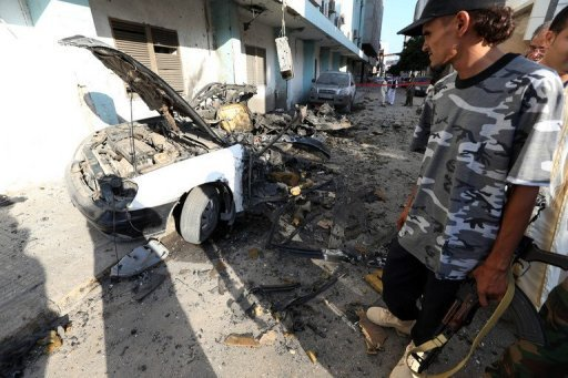 Libyans inspect the remains of a vehicle near the Ministry of Interior in Tripoli after twin blasts killed two people in the Libyan capital early on August 19. Libyan security services on Monday announced the arrests of a number of people suspected to be behind the double car bomb attack