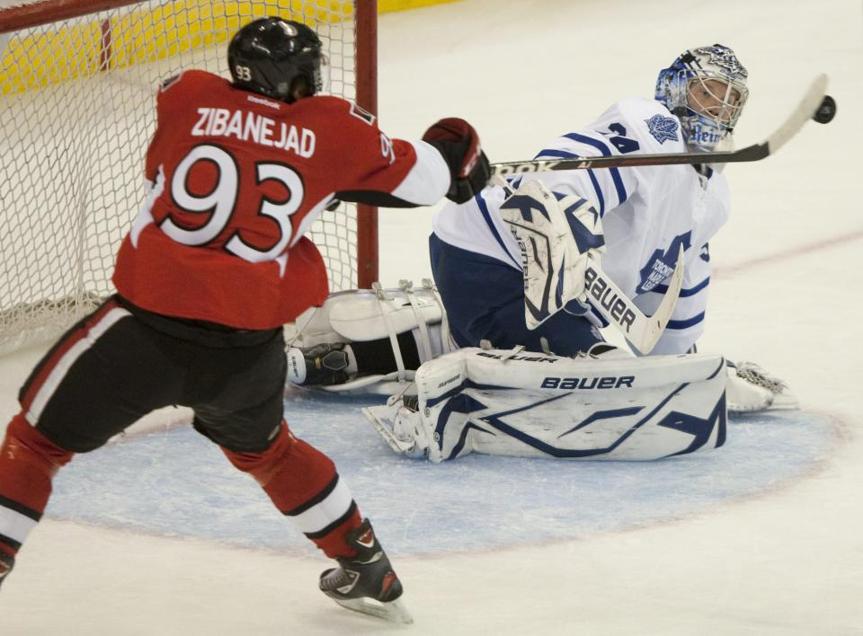 Ottawa Sentaors' Mika Zibanejad tips the puck past Toronto Maple Leafs goalie James Reimer to open the scoring during the first period of an NHL hockey game in Ottawa, Tuesday, Sept. 27, 2011. (AP Photo/The Canadian Press, Adrian Wyld)