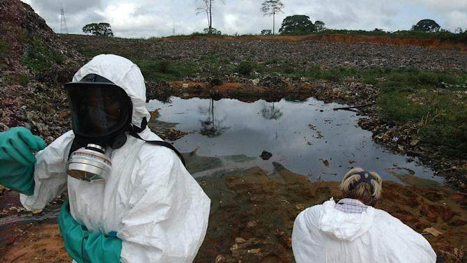 ADDS ATTRIBUTION TO IVORIAN AUTHORITIES FILE In this Sept. 17, 2006 file photo, waste removal experts work to remove hazardous black sludge from a garbage dump in Abidjan, Ivory Coast. A new report published Tuesday, Sept. 25, 2012 is calling on British authorities to investigate multinational oil trader Trafigura over a 2006 toxic waste dumping scandal that Ivorian authorities say killed at least 15 people and affected tens of thousands more in Ivory Coast's commercial capital of Abidjan.(AP Photo, File)