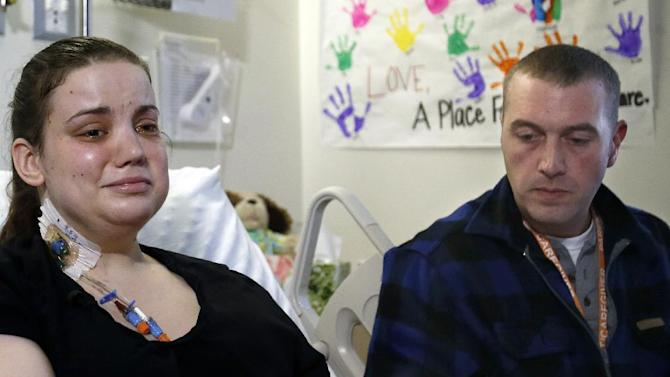 Washington mudslide survivor Amanda Skorjanc, left, talks to the media with her partner Ty Suddarth at Harborview Medical Center, Wednesday, April 9, 2014, in Seattle. On March 22, Skorjanic said she was trapped in a pocket formed by her broken couch and pieces of her roof with her infant son. Skorjanic had two broken legs and a broken arm. (AP Photo/The Herald, Dan Bates, Pool)