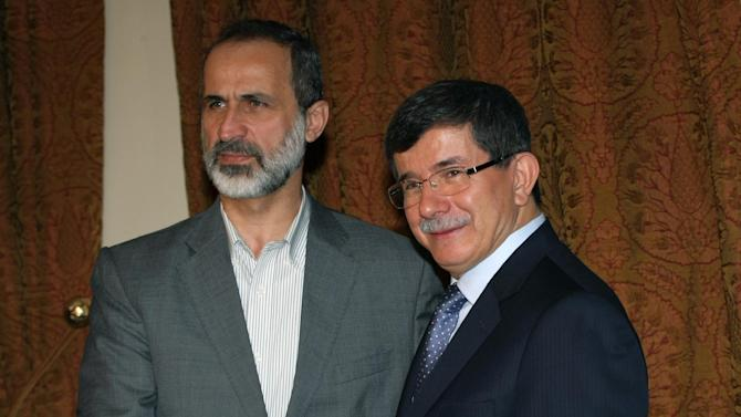 Turkey's Foreign Minister Ahmet Davutoglu, right, and head of the new Syrian National Coalition for Opposition and Revolutionary Forces Mouaz al-Khatib shake hands before a meeting in Ankara, Turkey, Friday, Nov. 23, 2012. (AP Photo/Burhan Ozbilici)