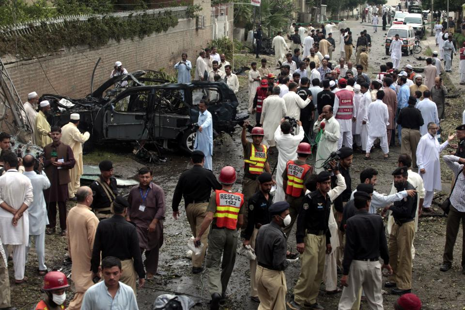 Officials and rescue volunteers gather at the bombing site in Peshawar, Pakistan on Monday, Sept. 3, 2012.  A car filled with explosives rammed into a U.S. government vehicle on Monday, killing a number of Pakistanis and wounding over a dozen others, police said. (AP Photo/Mohammad Sajjad)