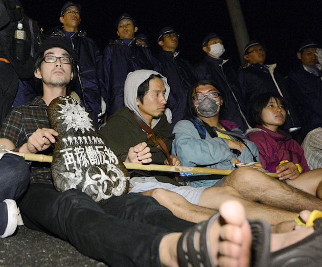 People sit in protest on a road near the entrance to the Ohi nuclear power plan in Ohi town, Fukui, western Japan early Sunday, July 1, 2012. Ohi No. 3 reactor will be switched on Sunday for the first
