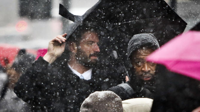 Commuters wait at a taxi stand outside Penn Station during snowfall on Friday, March 8, 2013 in New York.  A very wet snow is causing slippery road conditions in the metropolitan area. Snow flurries are expected to continue until about noon before changing to rain.  (AP Photo/Bebeto Matthews)