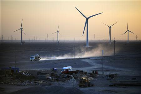 A construction site is seen near wind turbines for generating electricity at a wind farm in Guazhou, 950km northwest of Lanzhou, Gansu Province