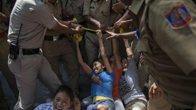 Indian policewomen detain Tibetan youth activists during a protest to highlight Chinese control over Tibet, outside the Hyderbad House in New Delhi, India, Thursday, Sept. 18, 2014. Several protests organized by exiled Tibetans were held in India on occasion of the visit of Chinese President Xi Jinping to India. (AP Photo/Tsering Topgyal)