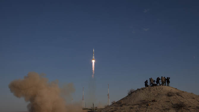 In this photo provided by NASA, members of the media photograph the Russian Soyuz rocket as it launches with Expedition 33/34 crew members, Soyuz Commander Oleg Novitskiy, Flight Engineer Kevin Ford of NASA, and Flight Engineer Evgeny Tarelkin of ROSCOSMOS to the International Space Station on Tuesday, Oct. 23, 2012, in Baikonur, Kazakhstan. Ford, Novitskiy and Tarelkin will be on a five-month mission aboard the International Space Station.  (AP Photo/NASA,Bill Ingalls)