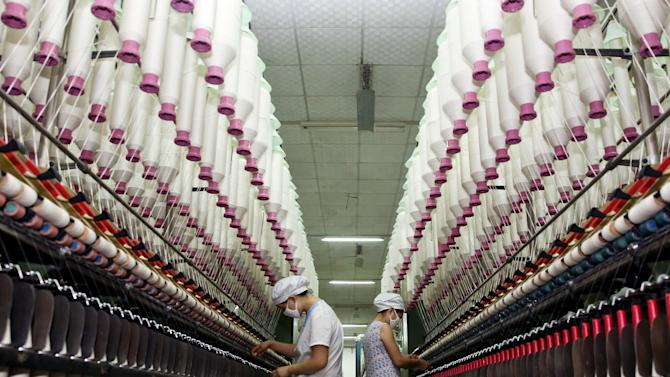 In this photo taken Wednesday Jan. 16, 2013, women work at a textile factory in Jiujiang city in central China's Jiangxi province. China's trade growth surged in January but much of the increase was driven by the traditional Lunar New Year holiday. Export growth accelerated to 25 percent from the previous month's 14.1 percent as companies rushed to fill orders before shutting down for a holiday break of up to two weeks. (AP Photo) CHINA OUT