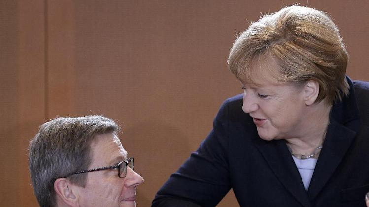 German Foreign Minister Guido Westerwelle, left, and German Chancellor Angela Merkel talk as they arrive for the weekly cabinet meeting at the chancellery in Berlin, Germany, Thursday, Dec. 6, 2012. (AP Photo/Michael Sohn)