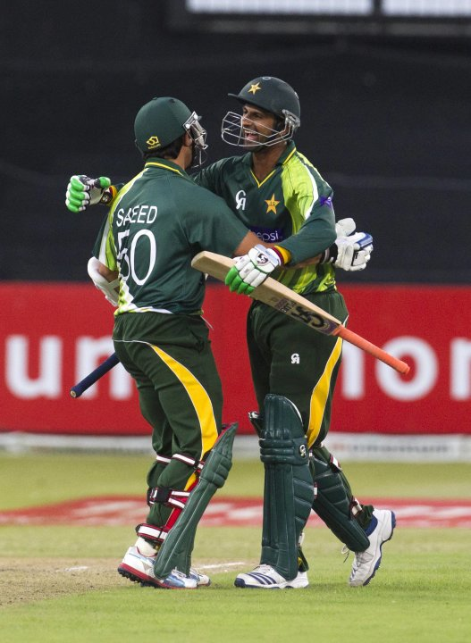 Pakistan's Ajmal and Malik celebrate winning their fourth One Day International cricket match against South Africa in Durban