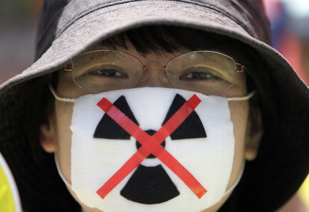 "An anti-nuclear protester waits to begin a march through downtown Tokyo Monday, July 16, 2012. Tens of thousands of people gathered at a Tokyo park, demanding ""Sayonara,"" or goodbye, to nuclear power as Japan prepares to restart yet another reactor, and expressed outrage over a report that blamed culture on the Fukushima disaster. (AP Photo/Greg Baker)"