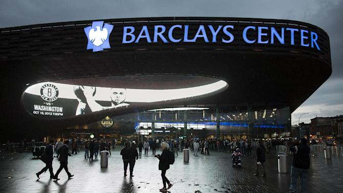FILE - This Oct. 15, 2012 file photo shows spectators arriving at the Barclays Center for a preseason NBA basketball game between the Brooklyn Nets and the Washington Wizards, in the Brooklyn borough of New York. Brooklyn is a sports town again, thanks to a sparkling new $1 billion arena and a Russian billionaire who parked his basketball team there. (AP Photo/John Minchillo, File)