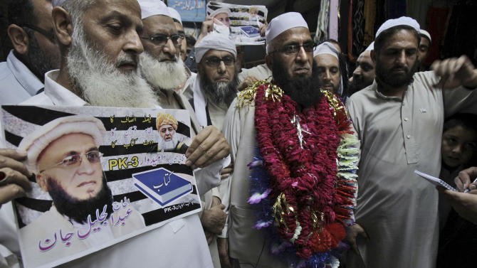 In this Tuesday, April 16, 2013 photo, Maulana Jalil Jan, second right, a candidate of Jamiat Ulema-e-Islam, is surrounded by supporters while touring a market in Peshawar, Pakistan. Moderate politicians from some of Pakistan's most violent areas are defying the threat of violence to run in upcoming nationwide elections, but they're increasingly turning to social media and phone calls that allow them to campaign from a distance. (AP Photo/Mohammad Sajjad)