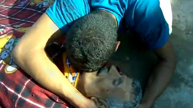 This citizen journalism image made from video provided by Shaam News Network SNN, purports to show a man mourning a victim killed by violence that, according to anti-regime activists, was carried out by government forces in Tremseh, Syria about 15 kilometers (nine miles) northwest of the central city of Hama, Thursday, July 12, 2012. The accounts, some of which claim more than 200 people were killed in the violence Thursday, could not be independently confirmed, but would mark the latest in a string of brutal offensives by Syrian forces attempting to crush the rebellion. (AP Photo/Shaam News Network, SNN) THE ASSOCIATED PRESS IS UNABLE TO INDEPENDENTLY VERIFY THE AUTHENTICITY, CONTENT, LOCATION OR DATE OF THIS IMAGE