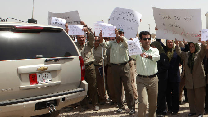 Members of the Mujahedeen-e-Khalq organization chant slogans and hold banners during a tour organized by the Iraqi government for foreign diplomats in Baghdad, Iraq, Tuesday, Sept. 11, 2012. Iraq's government has given foreign diplomats a rare look inside a refugee camp housing Iranian exiles, as Baghdad seeks international help resettling them in another country. Baghdad's Shiite-led government considers the Mujahedeen-e-Khalq a terrorist organization that is living in the country illegally. The government organized Tuesday's visit to Camp Liberty outside the capital, where 2,300 members of the group live, to speed their departure. The MEK is an opposition group to Tehran's clerical regime and cannot return to Iran. They were given sanctuary in Iraq by Saddam Hussein decades ago. (AP Photo/Hadi Mizban)