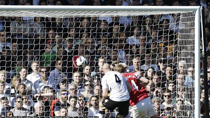 Arsenal's Per Mertesacker, right, heads the ball to score against Fulham during their English Premier League soccer match at the Craven Cottage ground in London, Saturday, April 20, 2013. Arsenal won the match 1-0. (AP Photo/Lefteris Pitarakis)