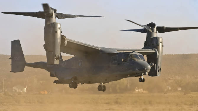 FILE - In this June 7, 2007 file photo, a CV-22 Osprey aircraft stationed at Kirtland Air Force Base kicks up a cloud of dust as it touches down at the Grants/Milan Airport in Grants, New Mexico, USA. Gunfire hit three U.S. military CV-22 Osprey aircraft Saturday, Dec. 21, 2013 trying to evacuate American citizens in Bor, the capital of the remote region of Jonglei state in South Sudan, that on Saturday became a battle ground between South Sudan's military and renegade troops, officials said, with four U.S. service members wounded in the attack. (AP Photo/Gallup Independent, Matt Hinshaw, File)