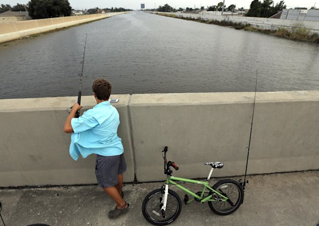 Dylan Lacoste, 14, fishes from the 17th Street Canal bridge Monday, Aug. 27, 2012, in New Orleans. Seven years ago this week Hurricane Katrina hit New Orleans. Tropical Storm Isaac is churning it's wa