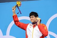 China's Sun Yang poses on the podium with his gold medal after winning the men's 400m freestyle swimming event at the London 2012 Olympic Games