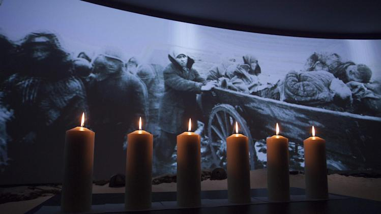 Memorial candles are lit in front of a photo taken during WWII showing refugees fleeing from the Nazis at a ceremony marking International Holocaust Remembrance Day in Russia's first Jewish Museum in Moscow, Russia, Sunday, Jan. 27, 2013. (AP Photo/Alexander Zemlianichenko Jr)