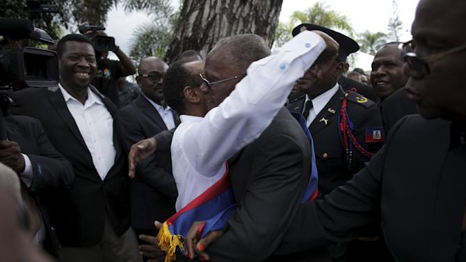 Provisional Haitian President Jocelerme Privert hugs an attendee to the Presidential inauguration at the gardens of the National Palace in Port-au-Prince
