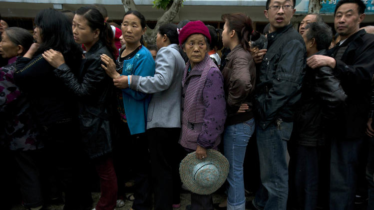 Residents line up for packets of instant noodles in the earthquake struck county of Lushan in southwestern China's Sichuan province, Monday, April 22, 2013. Saturday's earthquake in Sichuan province killed at least 186 people, injured more than 11,000 and left nearly two dozen missing, mostly in the rural communities around Ya'an city, along the same seismic fault where a devastating quake to the north killed more than 90,000 people in Sichuan and neighboring areas five years ago in one of China's worst natural disasters.(AP Photo/Ng Han Guan)