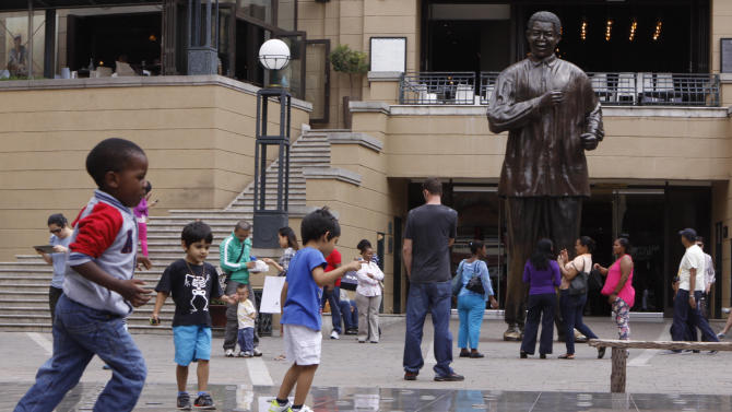 Children play beneath a giant statue of former South African President Nelson Mandela, center back, on Nelson Mandela Square in Sandton, Johannesburg, Sunday, March 10, 2013.  Mandela, spent a night in a hospital after he was admitted for scheduled tests, the presidency said Sunday. (AP Photo/Denis Farrell)