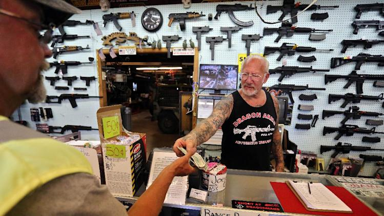 In this July 20, 2014 photo, with guns displayed for sale behind him